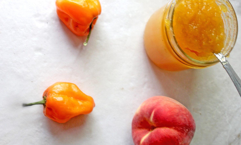 Habanero peppers and fresh peach beside open jar of Friends Drift Inn Peach Habanero Jam