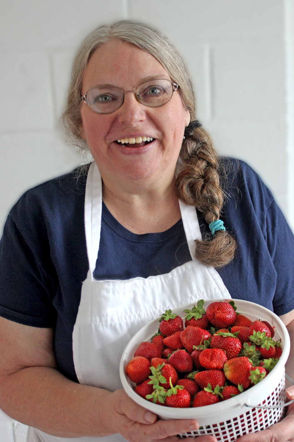 Joyce Pinson of Friends Drift Inn wearing bib apron and carrying bucket of fresh strawberries