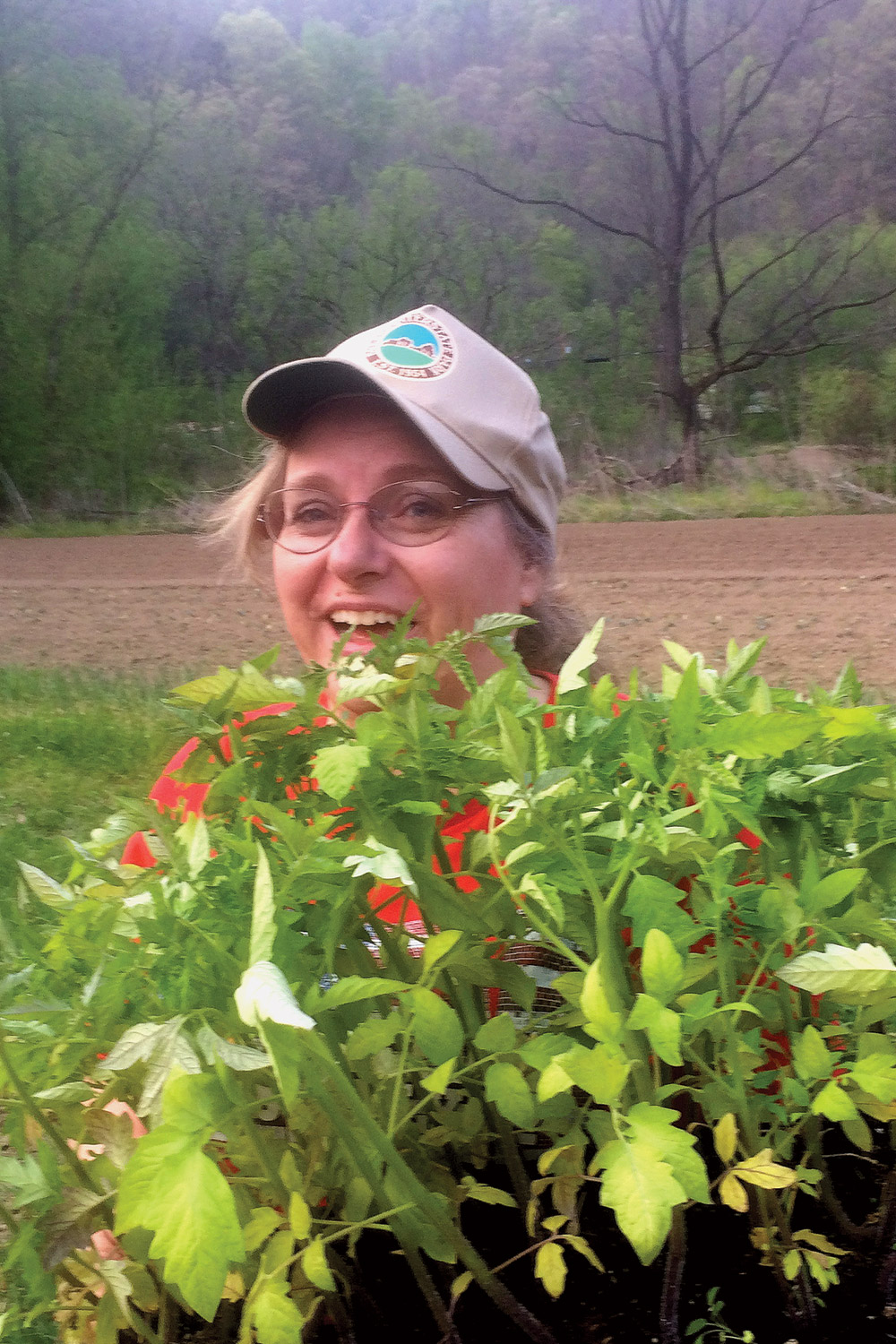 Joyce Pinson carrying tomato plants to the farm fields