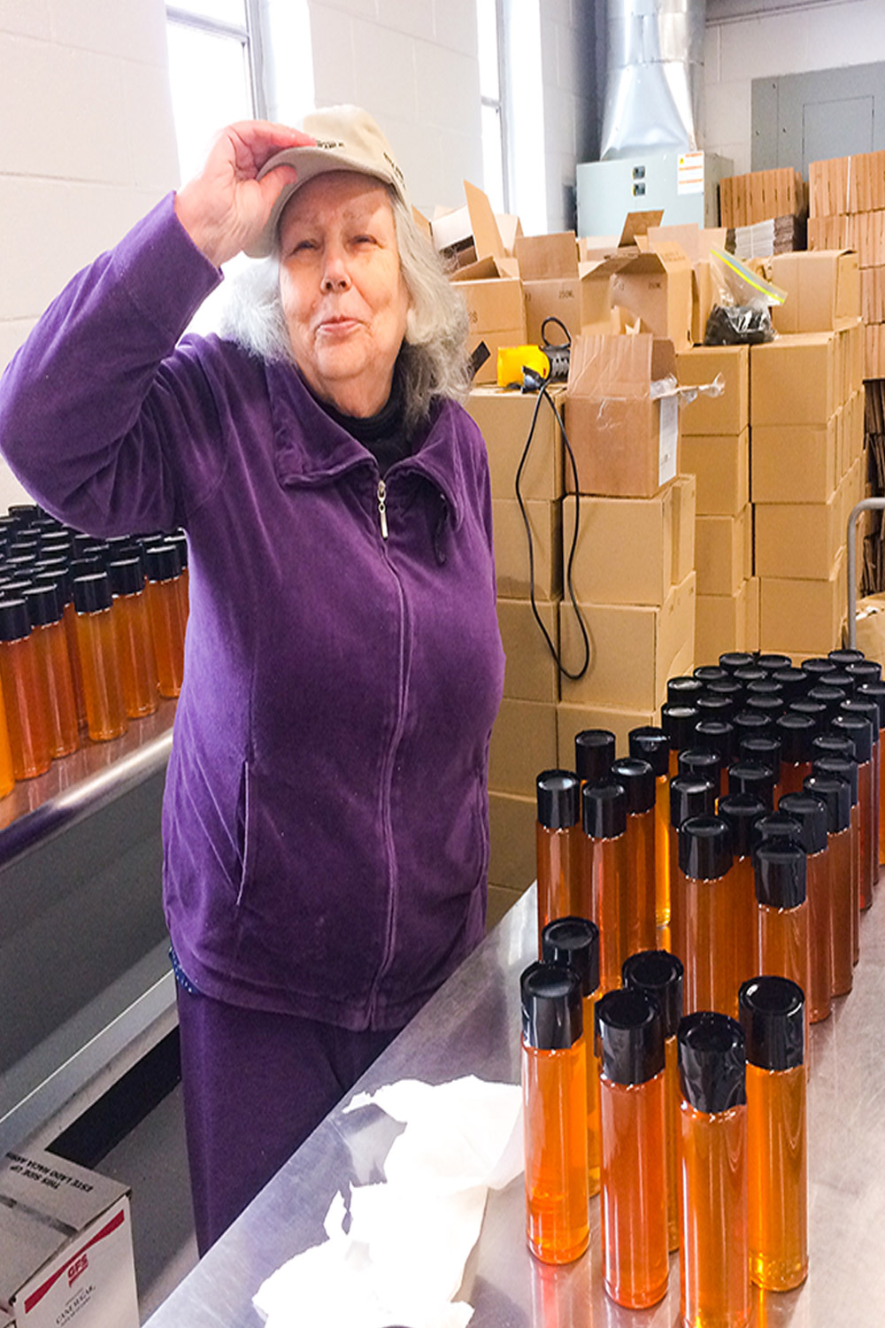 Momma tipping her ballcap standing amidst boxes and jars for shipping