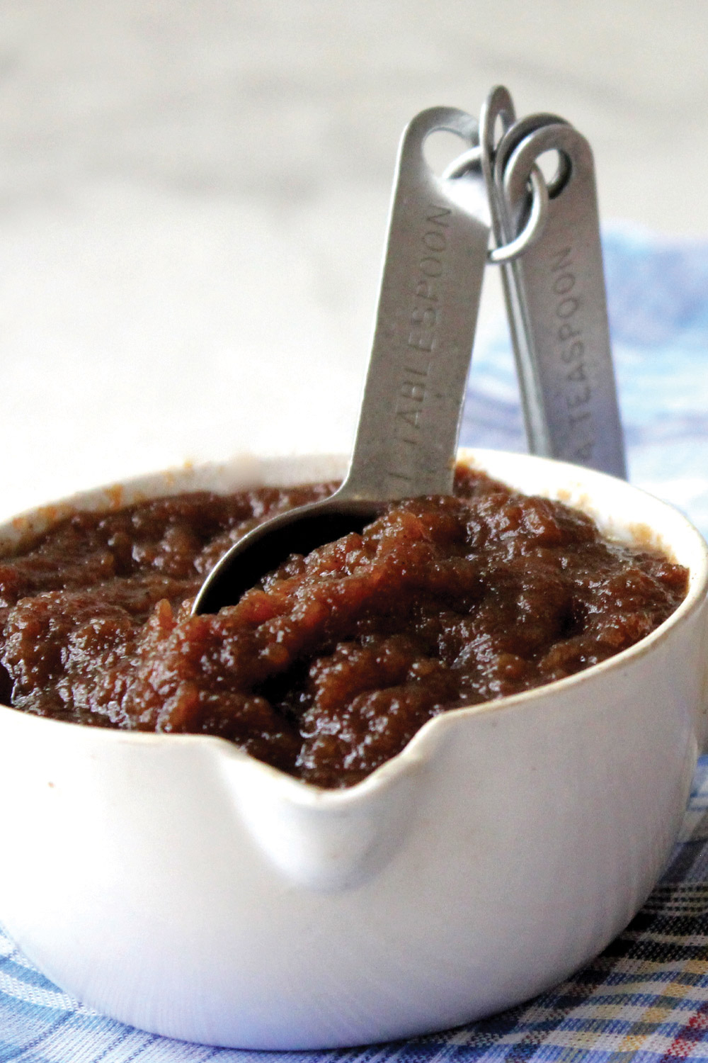 Measuring cup full of apple butter with measuring spoon standing in the thick brown apple butter