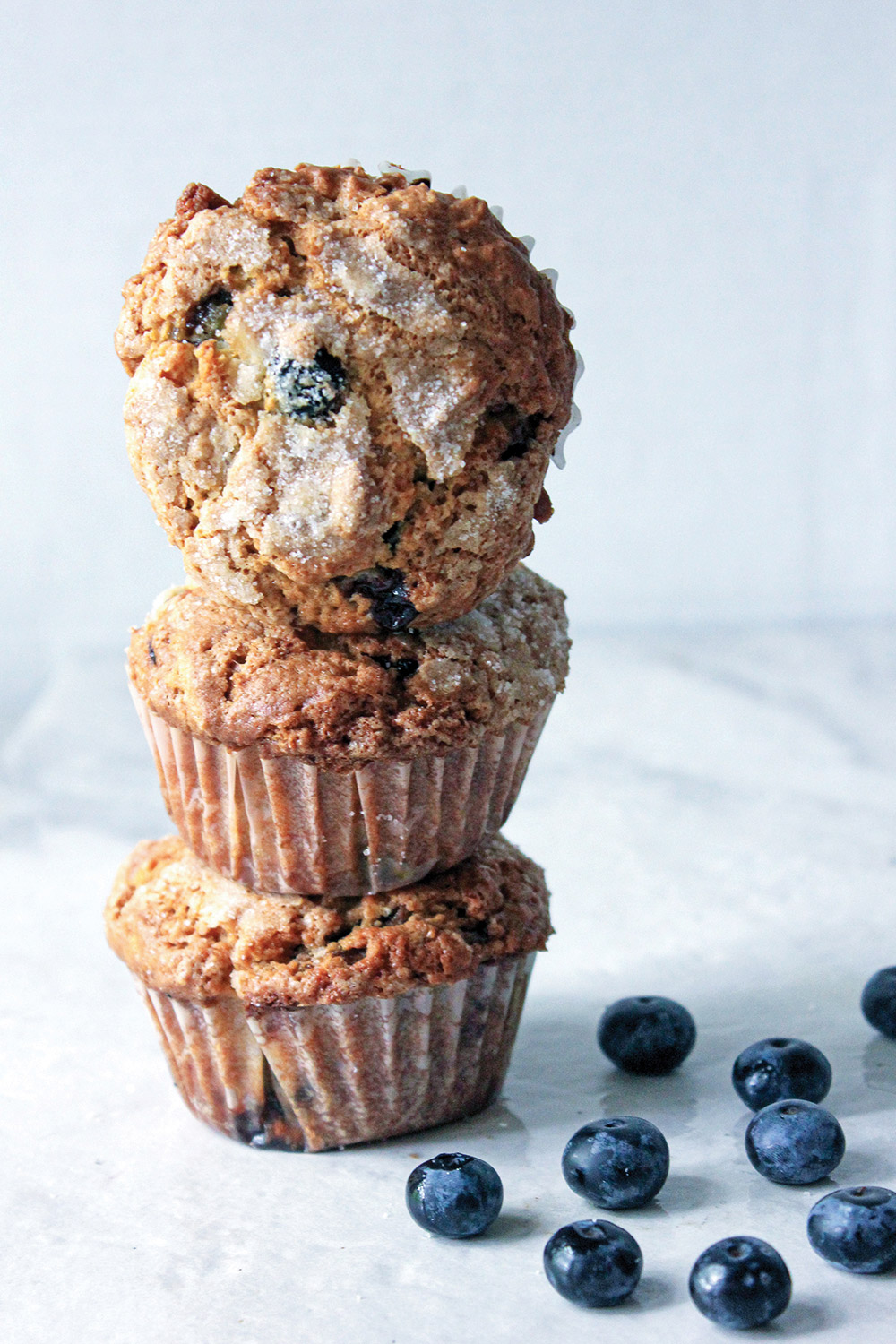 Three blueberry muffin tower with top muffin tilted to show sugar crusted top.  Blueberries in background.