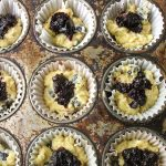 Shows blueberry muffins in tin, half full with blueberry jam spoooned in.