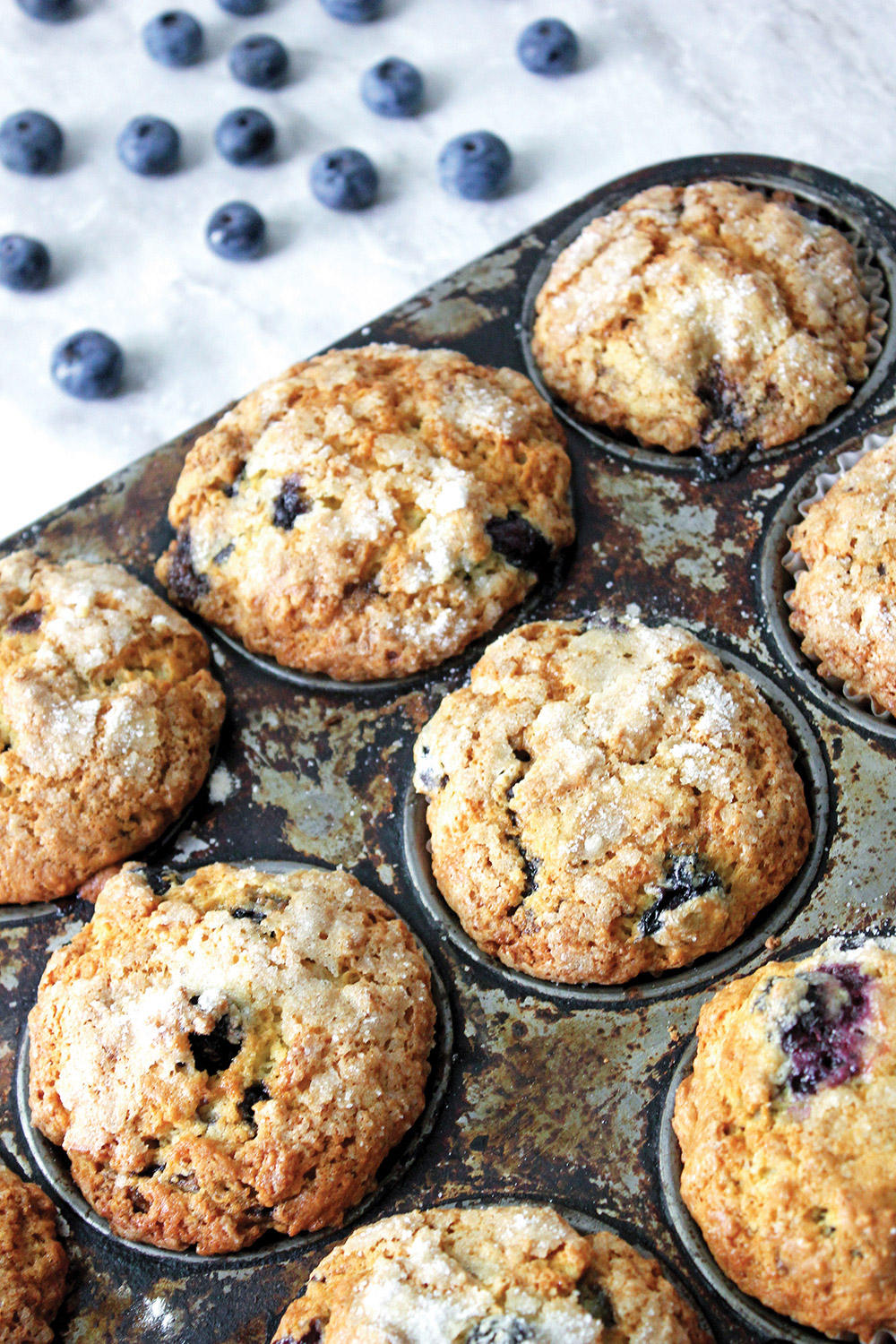 Blueberry muffins with sugar crusted crowns in muffin tin with blueberries in background.