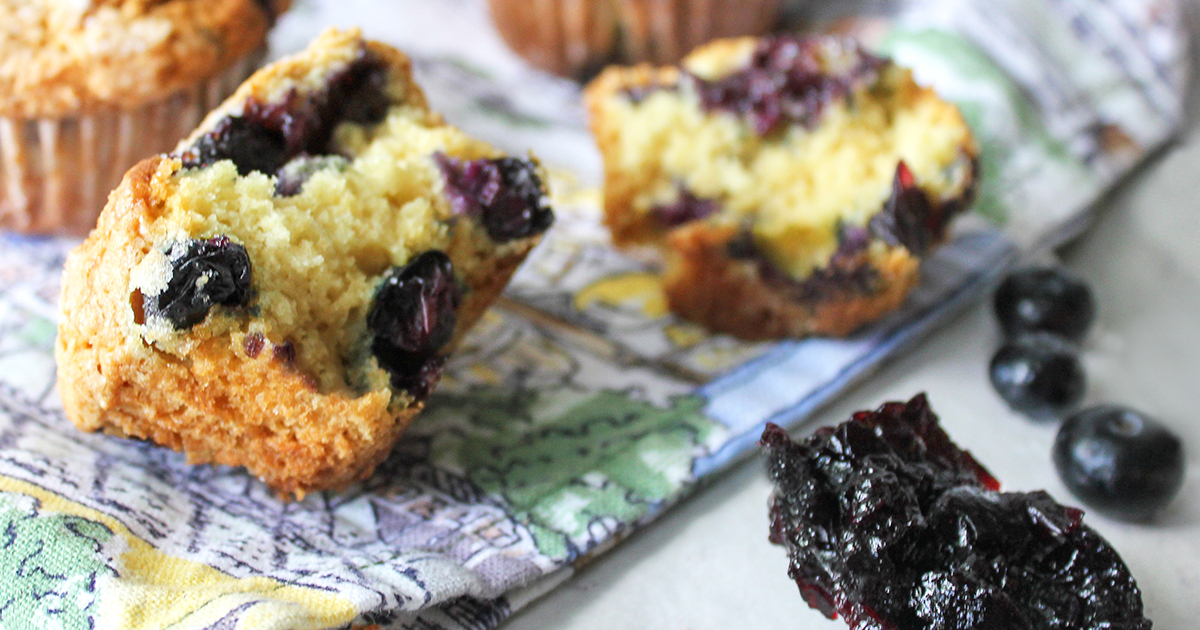 Blueberry Muffins broken in half to reveal jam filled center and blueberrys, sugar crusted top - sitting on a blue linen cloth