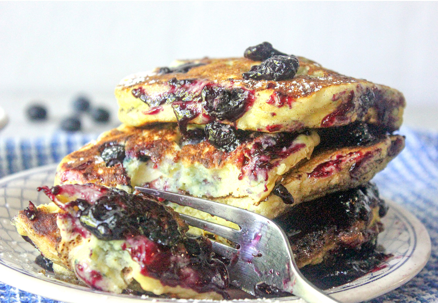 Stack of blueberry pancakes with a fork cutting through to show how fluffy they are.