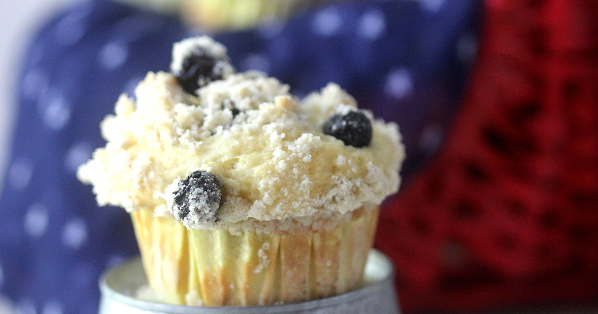 Single muffin with large top cardamom crumble topping studded with blueberries in front of a red, white, and blue basket of blueberry muffins