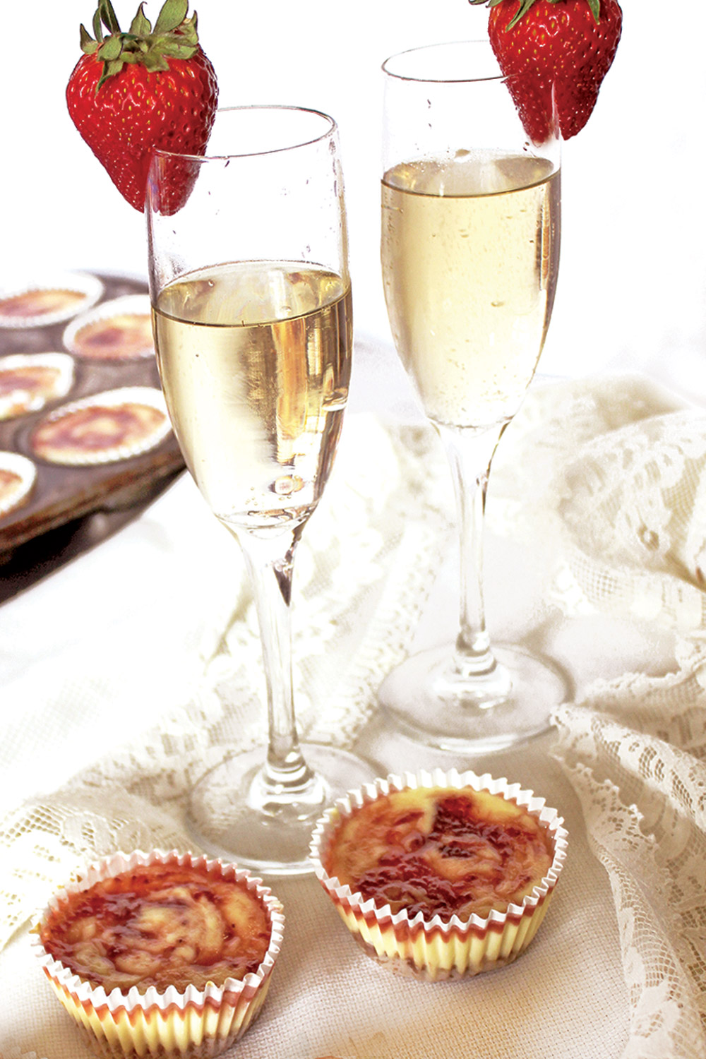 Pair of champagne flues on lace tablecloth with cheesecake strawberry jam swirls