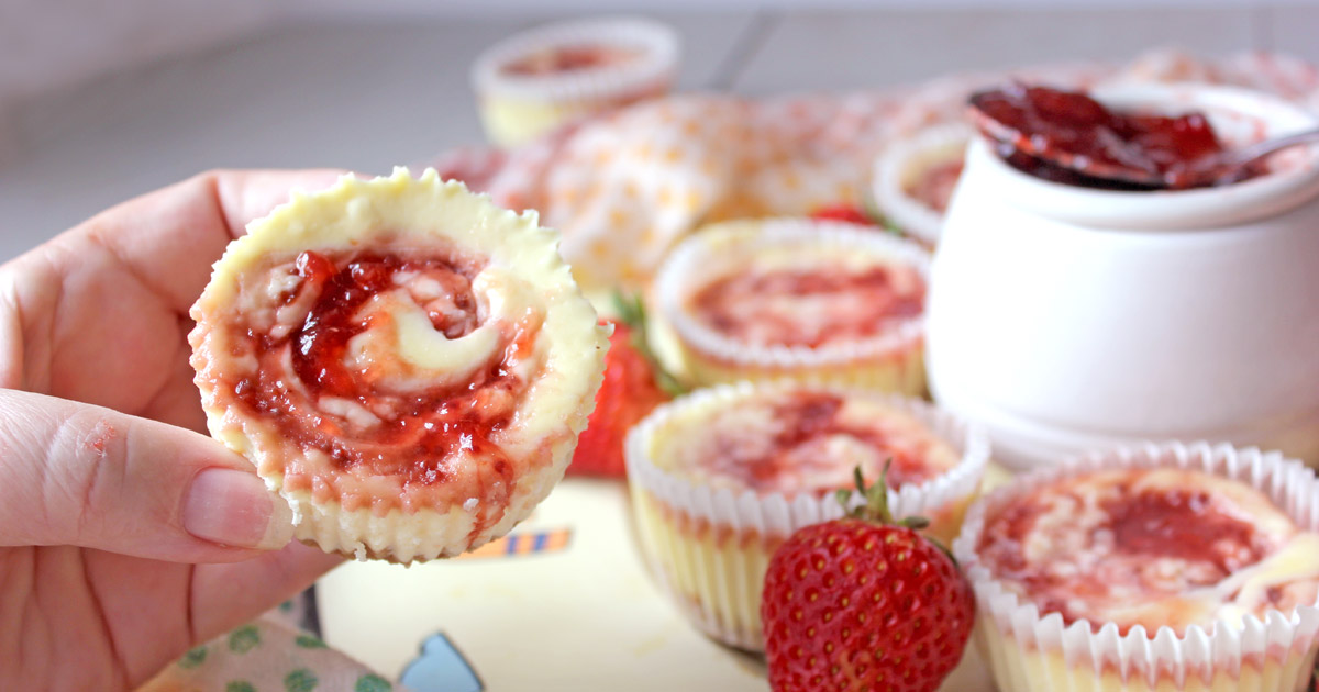 Hand with individual cheesecake with strawberry jam swirls - strawberries and desserts in background