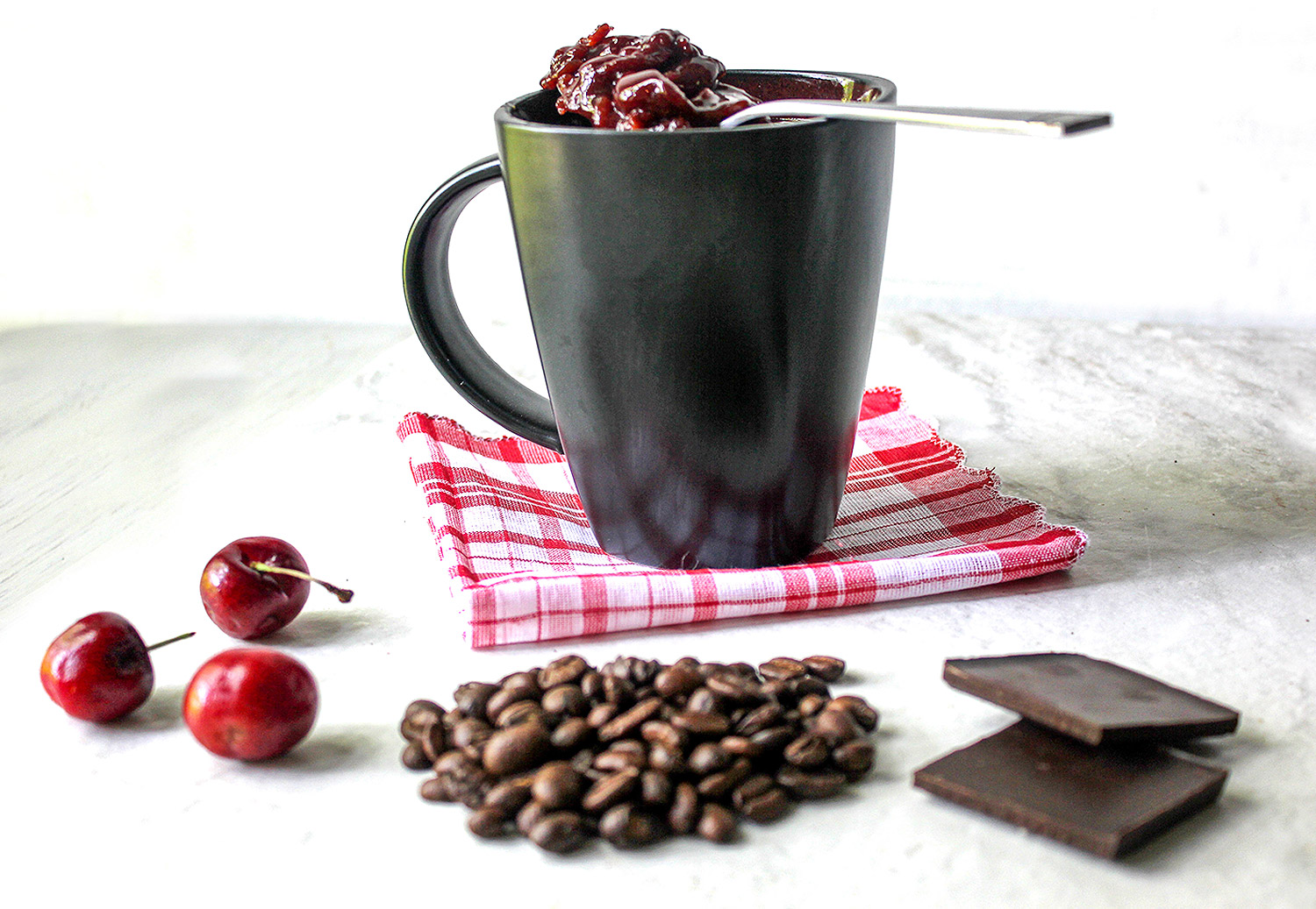 Tart fresh cherries, coffee beans, and two squares of chocolate in front of a black coffee mug that has a spoonful of chocolate cherry jam propped across the top . Coffee cup is on a red checked napkin.