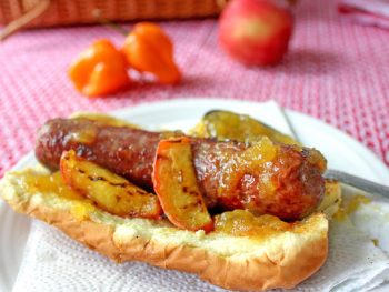 Grilled hot dog on bun with peach habanero jam glaze