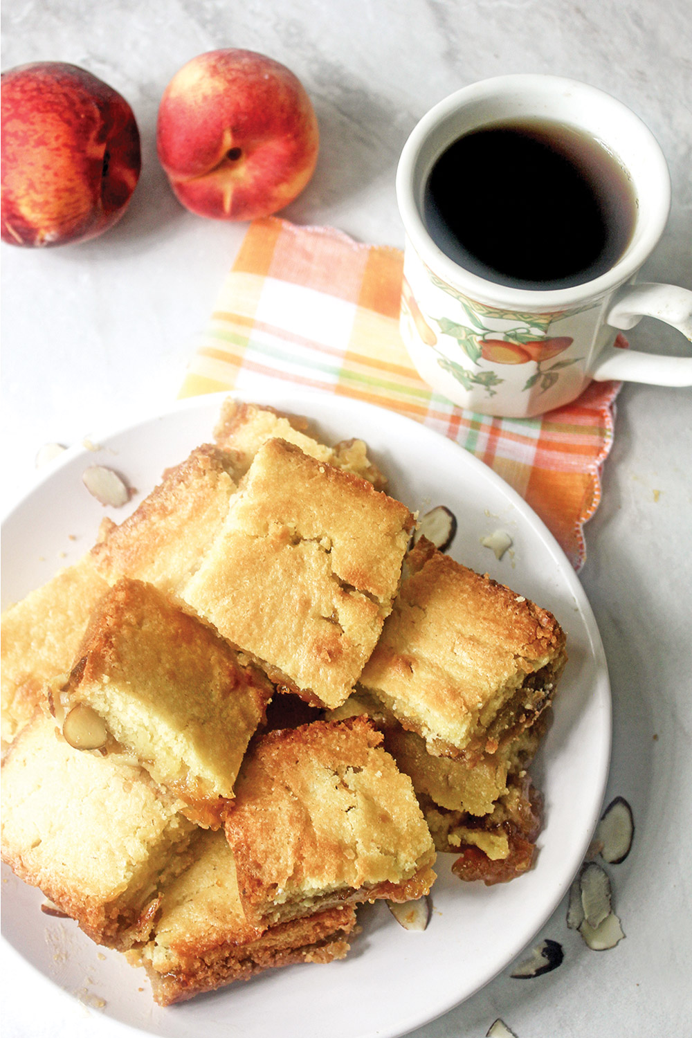Peach cobbler jam bars from overhead perspective with cup of coffee on a plaid napkin and fresh peaches in the background.