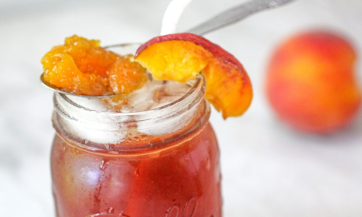 Peach Jam Sweet Tea Bourbon Cocktail in a mason jar garnished with jam spoon and a peach wedge.