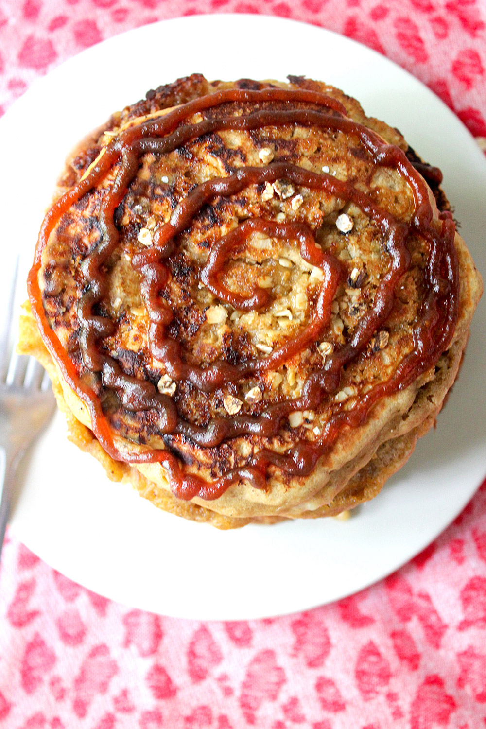 Overhead view of spiced apple butter pancakes showing spiral swirl of apple butter and oats struesel topping