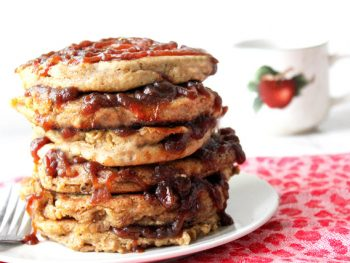 Tall stack of spiced apple butter pancakes oozing apple butter between layers and in a spiral swirl on top layer with an apple coffee cup in background