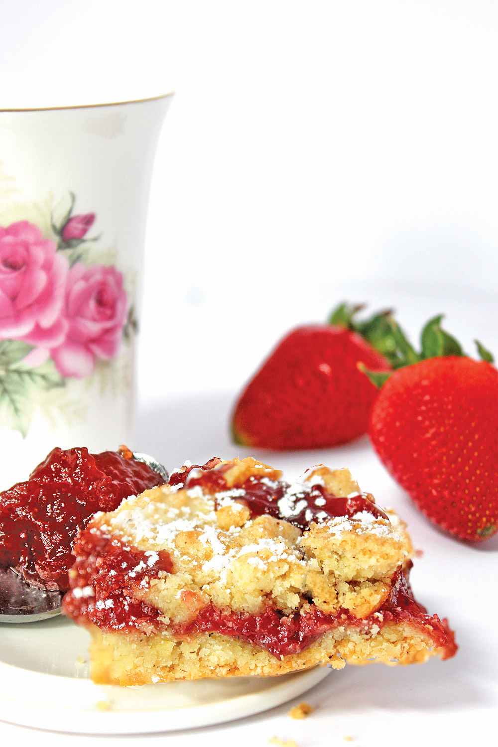 Strawberry Jam Bar plated with spoon of strawberry moonshine jam on side with teacup and fresh strawberries in background.