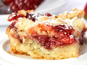 Strawberry jam bar on a white plate with a sprinkle of confectionary sugar