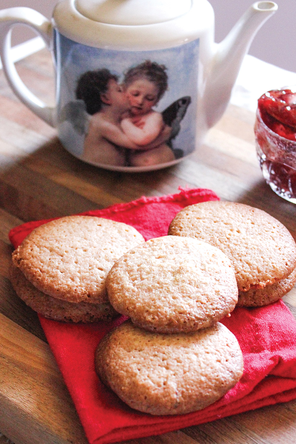 Strawberry jam sugar cookies on a red napkin with a porcelian tea pot in background featuring two cherubs kissing
