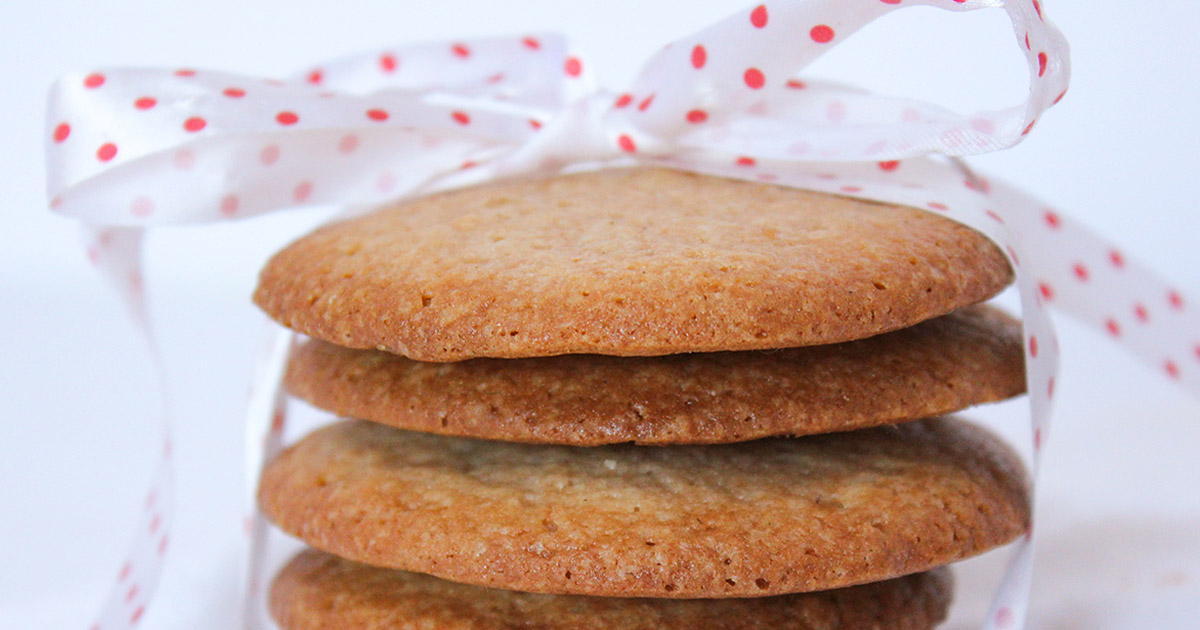 Stack of strawberry jam sugar cookies with a red and white ribbon bow on top
