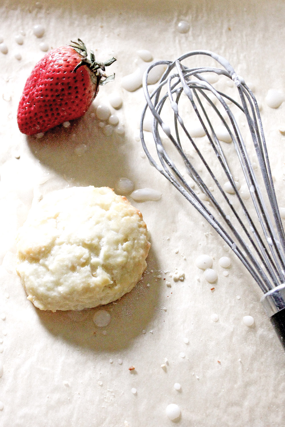 Kitchen setting-biscuit, strawberry, whisk on a floured surface