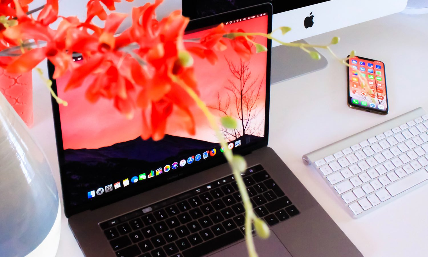 Vase of flowers superimposed over computer keyboarad, iphone, and screen.