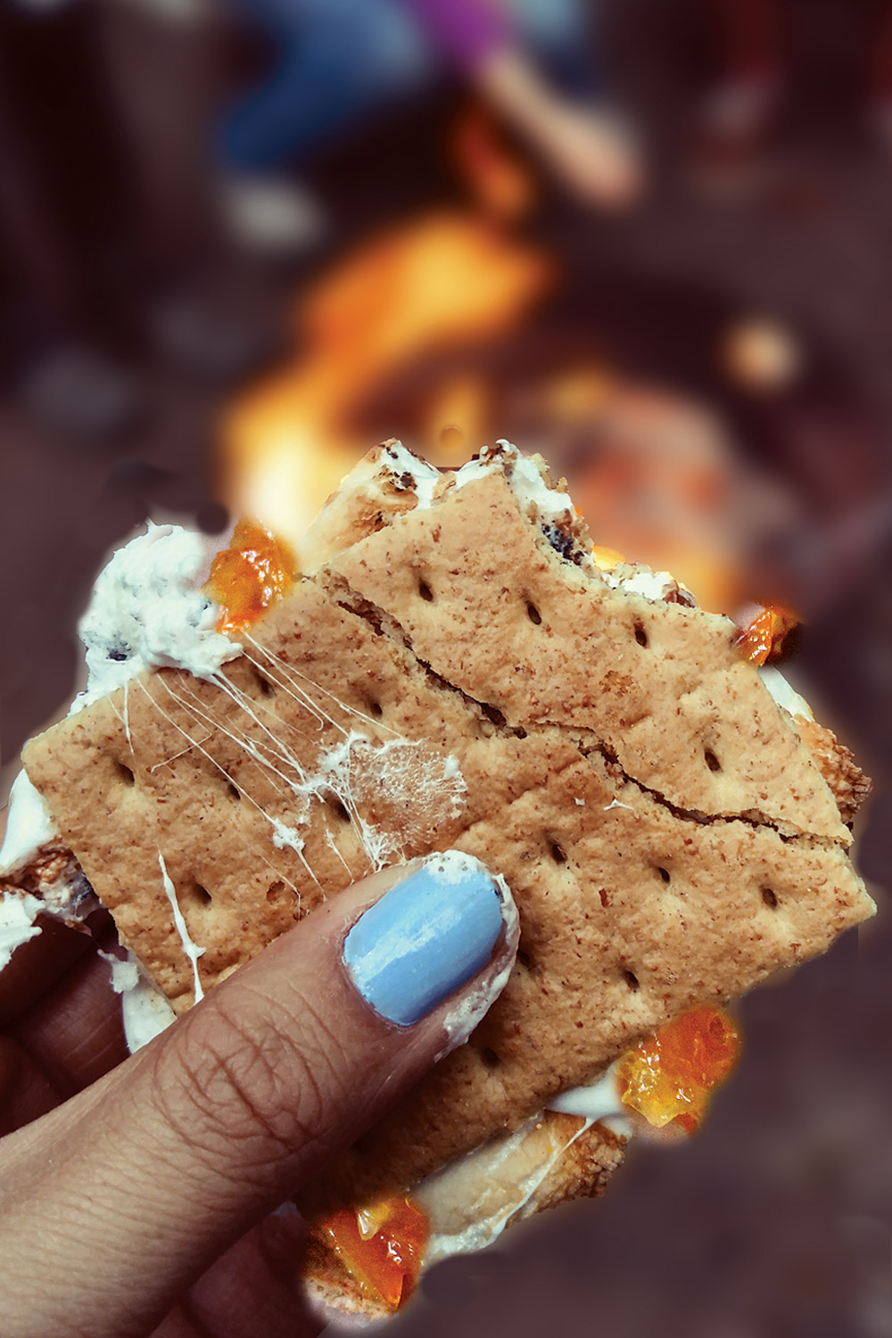Hand grasping a gooey orange marmalade s'more with campfire in background