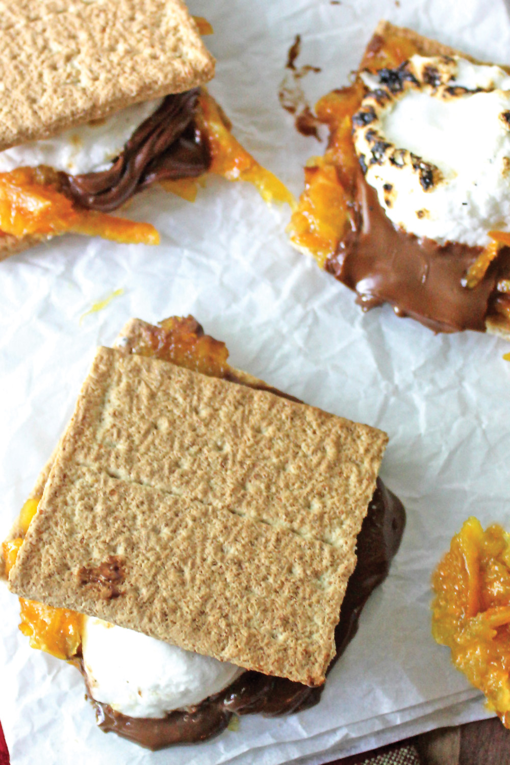 Orange marmalade smores with melted chocolate, roasted marshmallows perched on graham crackers resting on crumbled parchment paper