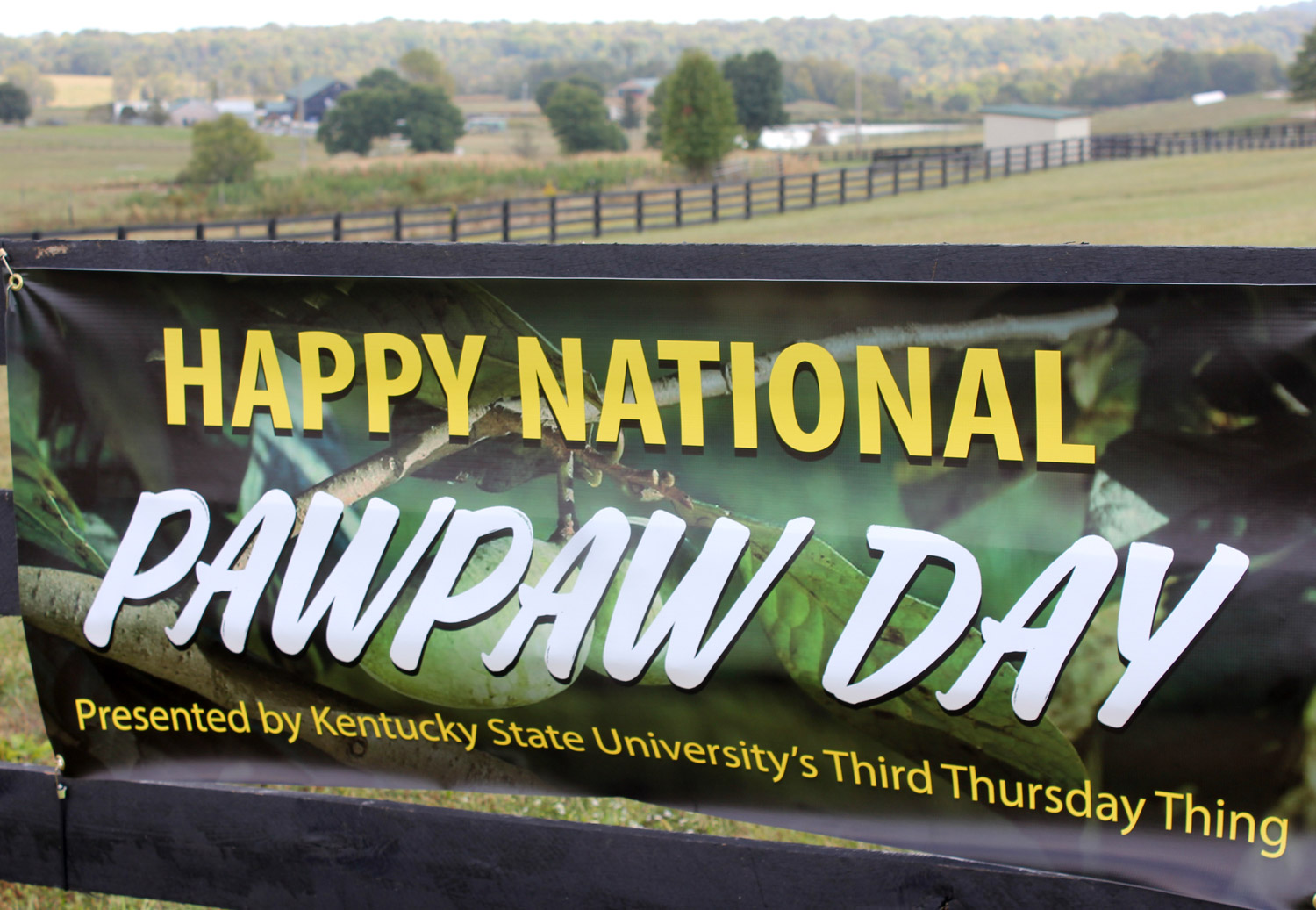 Banner on horse fence proclaiming National Pawpaw Day at KY State University in Frankfort