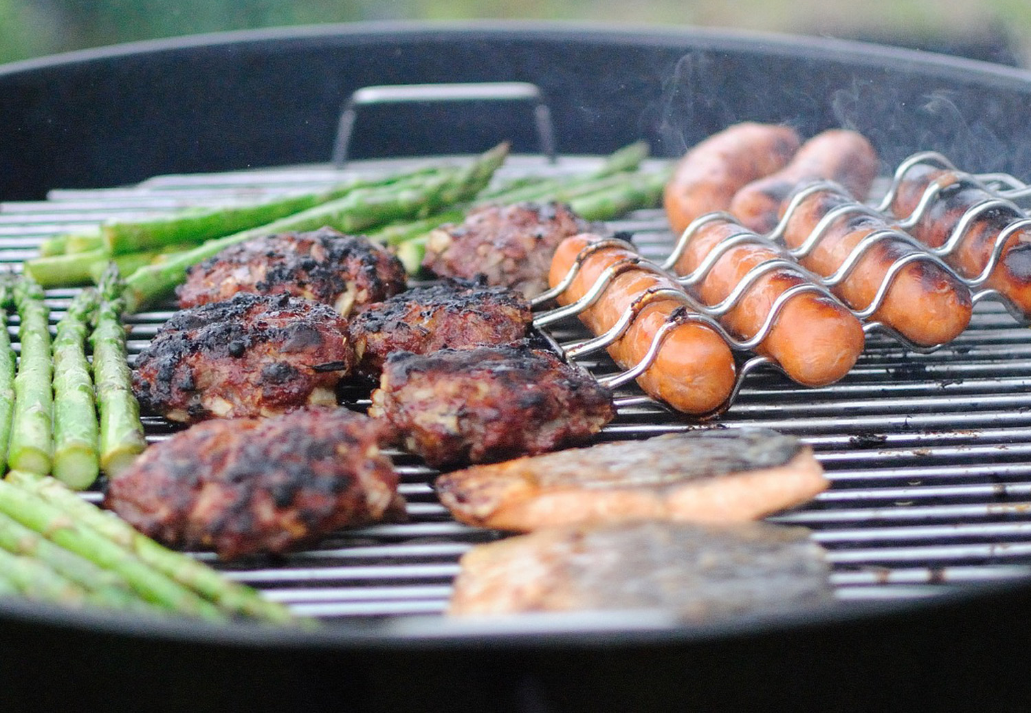 Backyard BBQ with charcoal grill loaded with hamburgers and hot dogs
