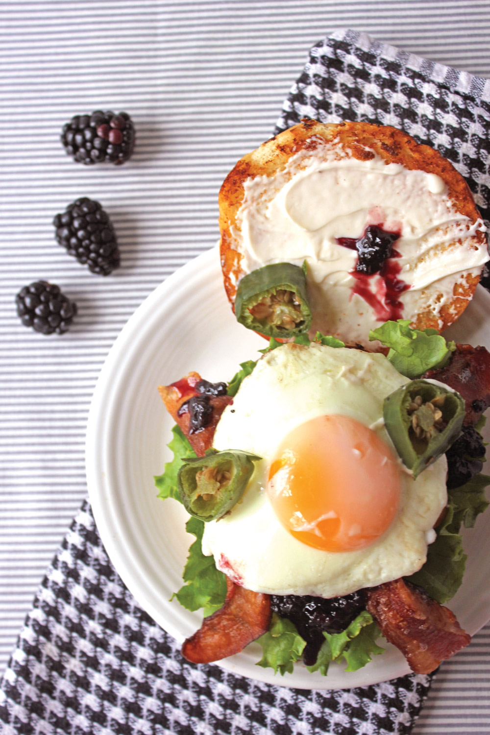Overhead view of burger with sunny side up egg, ackberry jam, jalepenos, and lettuce with blackberries on side