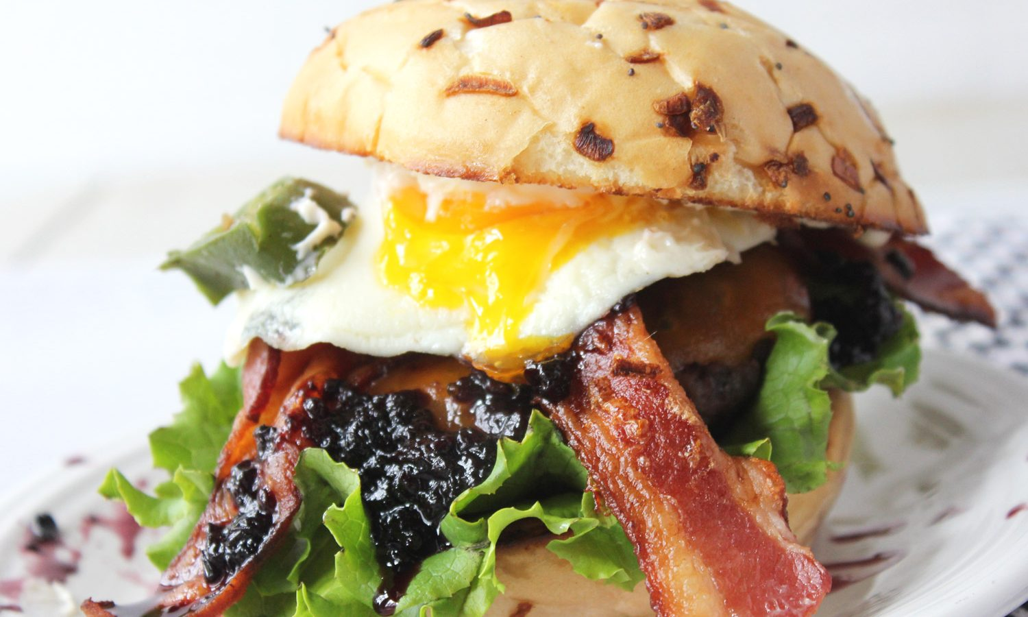Burger with egg on a onion bun with bacon, peppers, and blackberry jam