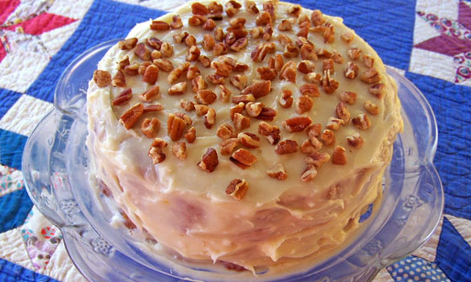 Pawpaw cake with frosting and nuts on top of a blue quilt