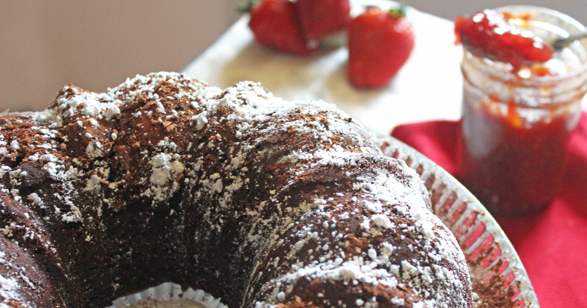 Chocolate Bundt Cake with strawberries and jam in background