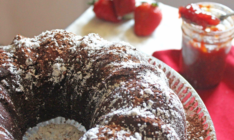 Chocolate Bundt Cake Next to Jam and Strawberries