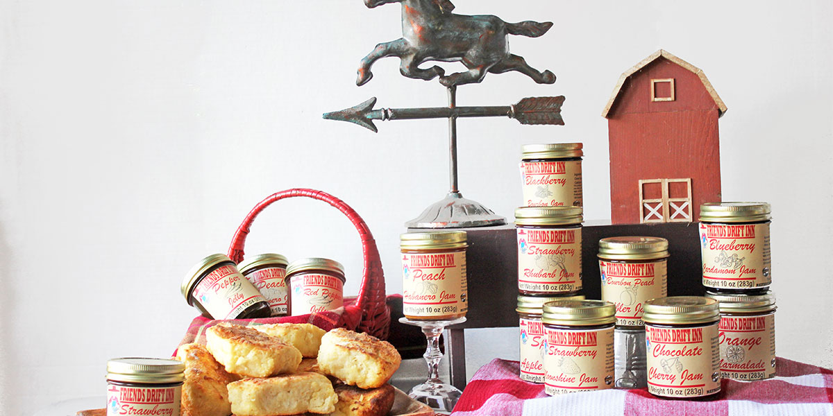 Friends Drift Inn jams and jellies with basket of biscuits, horse weather vane, and a wooden barn