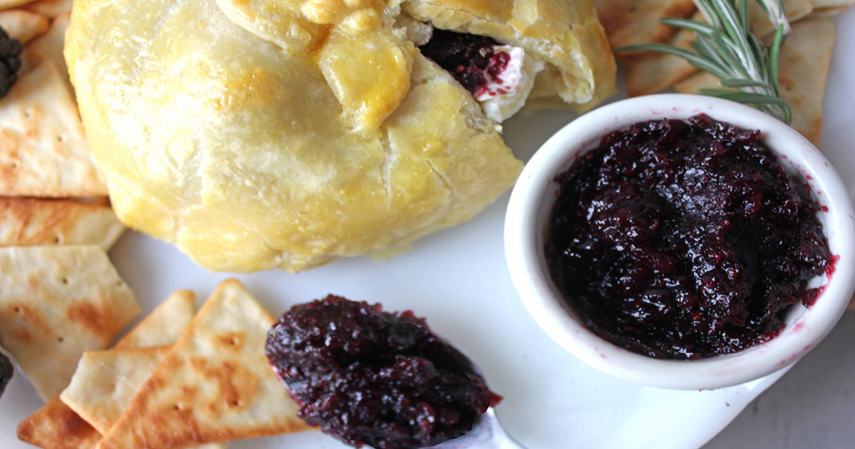 Baked brie in puff pastry with blackberry jam and on appetizer plate.