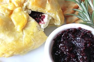 Baked brie berries with jam oozing from puff pastry.