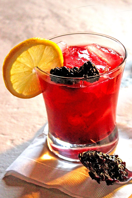 Blackberry Bramble gin cocktail in rocks glass with lemon wheel and blackberry garnish