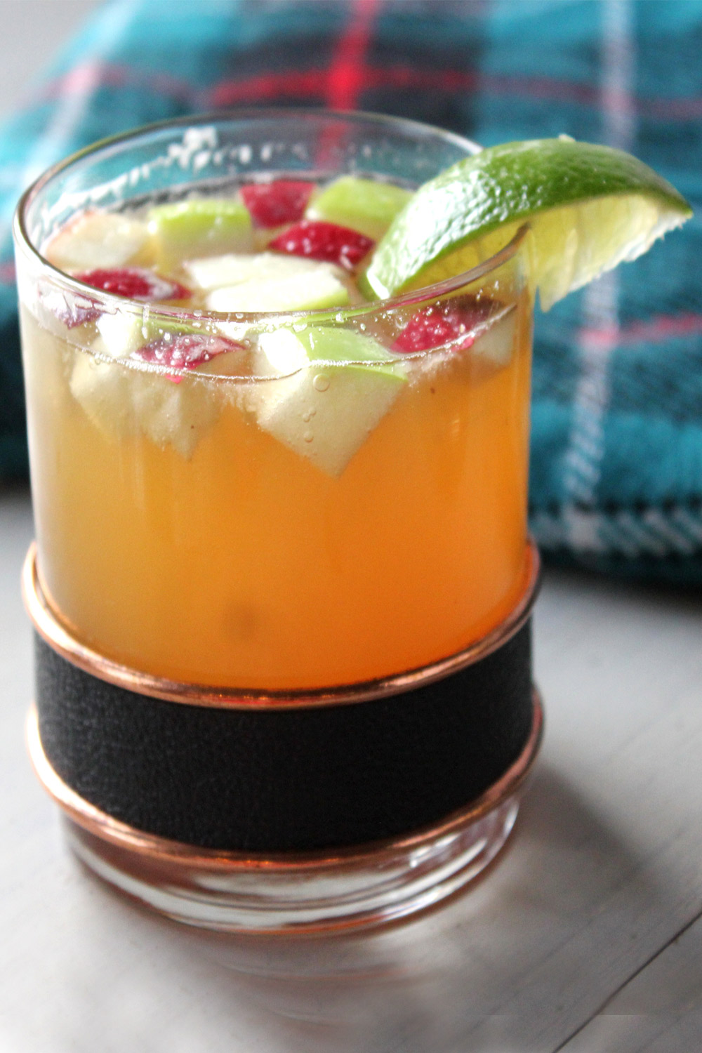 Bourbon and apple cider cocktail topped with red and green cubed apples and lime wedge