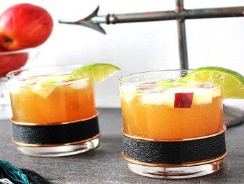 Two Bourbon Apple Cider Cocktails in vintage rocks glasses with bowl of apples in background