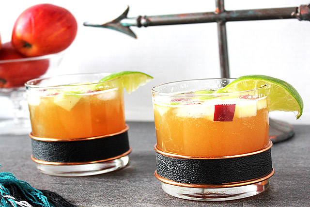 Two Bourbon Apple Cider Cocktails in vintage rocks glasses with bowl of apples in background
