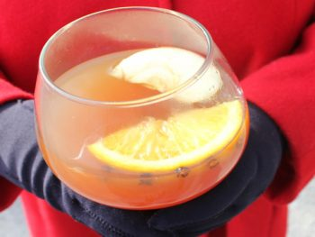Snifter bowl glass with apple cider bourbon wassai held in gloved hands next to a red wool coat