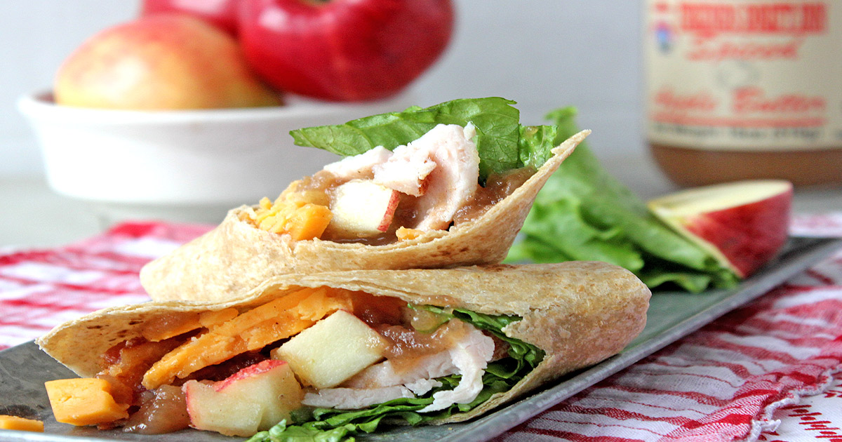Turkey wrap with fresh apples and jar of apple butter in background