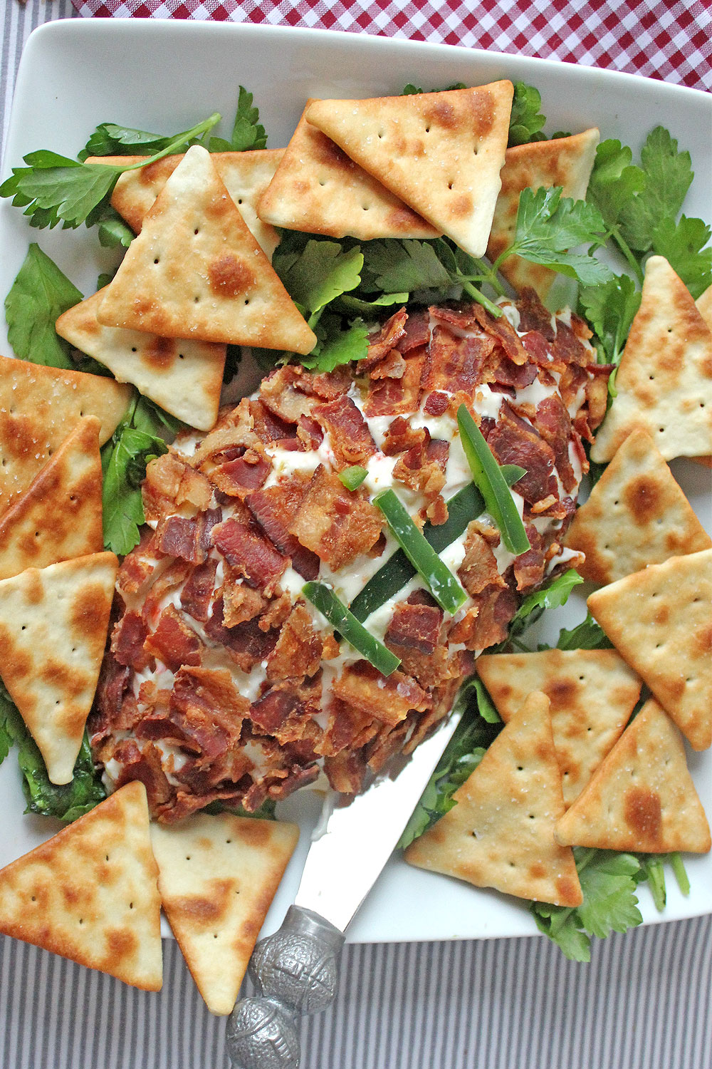 Pepper jelly and cream cheese football with bacon and jalapenos served on a platter with pita chips.